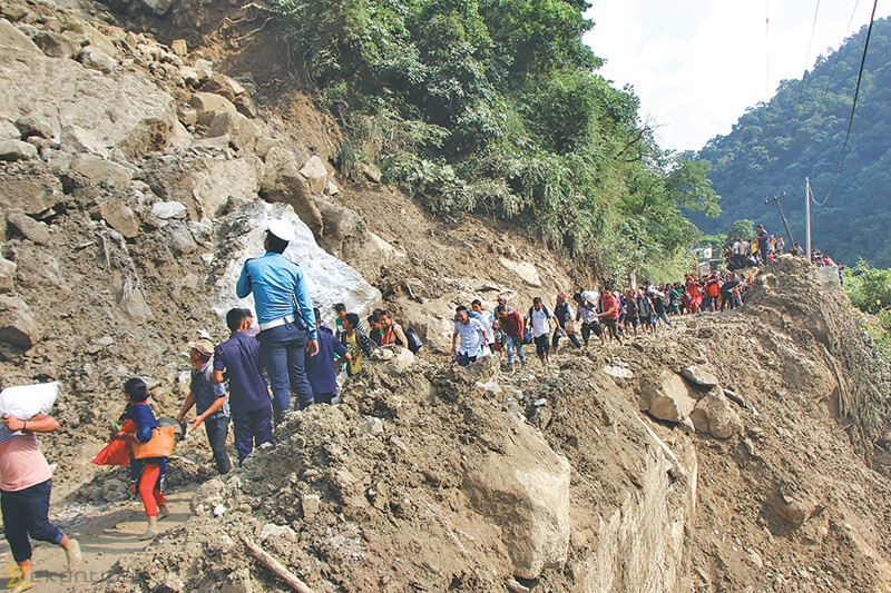 Passengers cross the landslide-hit section of the highway in Siddhababa, Palpa.