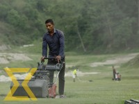 A worker cuts grass with a lawn mower at the army golf course in Gaurighat, Kathmandu, on Friday.