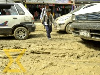 Children in school uniform try to cross the muddy road at Bouddha in the Capital on Friday.