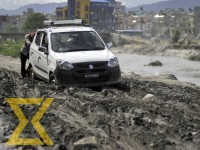 A man pushes a taxi that got stuck in a muddy road at Gatthaghar in Bhaktapur on Wednesday.