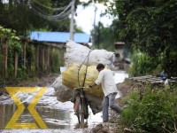 A scrap collector struggles to pass though a waterlogged road at Thapathali in Kathmandu on Wednesday.