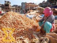 A worker crushes bricks at the reconstruction site of RatoMachhindranath temple in Bungamati, Lalitpur on Tuesday. The brick pieces which will later be turned into brick-powder to be used in grinding machine as mortar by mixing it with lime-powder. The mo