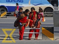 Women cross the railing as they cross the road at Kalanki, Kathmandu on Friday. People often cross the road haphazardly due to lack of road safety measures and zebra crossings. Chinese Company, which built the 10-km stretch from Kalanki to Koteshwor, the