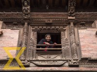 A Newari girl looks out of a window during the annual Vindyo Puja ritual at Sundari Chwok, Lalitpur on Saturday. People from Newar community worship Vindyo God believing that the deity brings prosperity in their business.