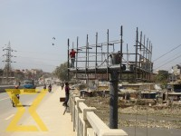 Workers prepare a structure to install a hoarding board at Balkhu in Kathmandu.