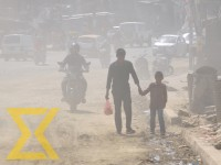 A man and his son walk on a dusty Kalanki-Nagdhunga road section on Saturday.